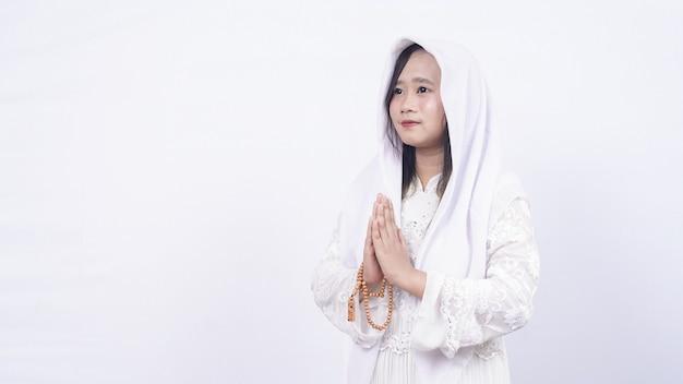 Asiatische muslimische frau, die gebetsperlen trägt, die gäste begrüßen