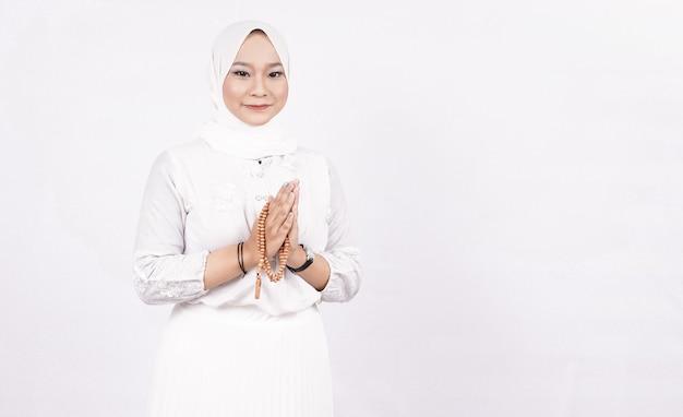 Asiatische muslimische frau, die gebetsperlen trägt, die gäste oder ied fitr-gruß im weißen raum begrüßen