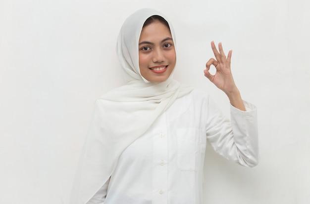 Asiatische muslimische frau, die hijab mit ok zeichengeste trägt