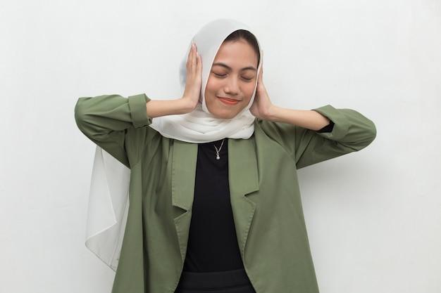 Asiatische muslimische frau, die ihre ohren bedeckt
