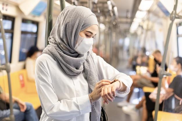 Asiatische muslimische frau, die medizinische gesichtsmaske trägt, um staub und infektionsvirus zu verhindern und smartwatch im öffentlichen skytrain-transitsystem zu suchen.