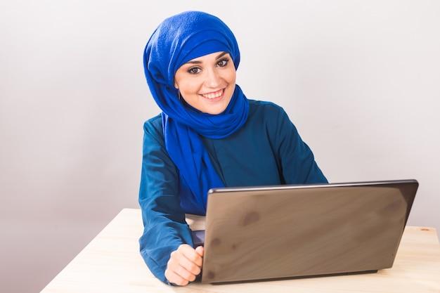 Asiatische muslimische frau, die mit computer-laptop arbeitet