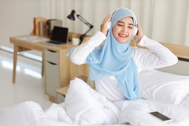 Asiatische muslimische frau, die musik hört
