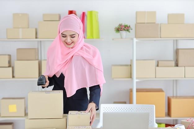Asiatische muslimische frau, die scanner mit paketkastenlieferung steht und hält.