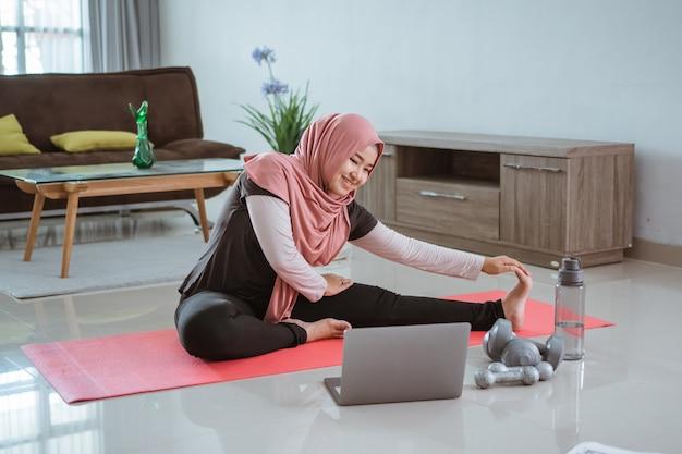 Asiatische muslimische frau, die übung und sport zu hause tut