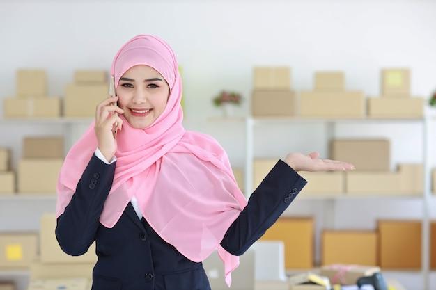 Asiatische muslimische frau im blauen anzug, der handy verwendet und etwas zur hand mit geschäftspaket zeigt