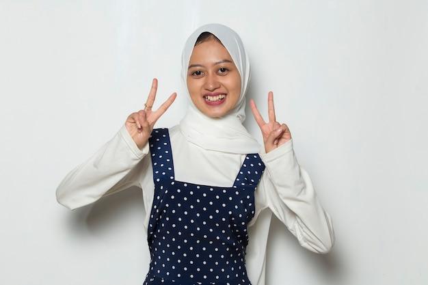 Asiatische muslimische frau im hijab, die frieden oder sieghandgeste zeigt