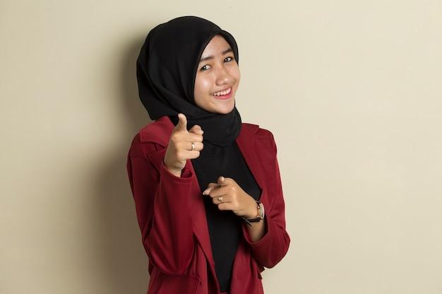 Asiatische muslimische frau im hijab lächelnd, während sie nach vorne zeigt
