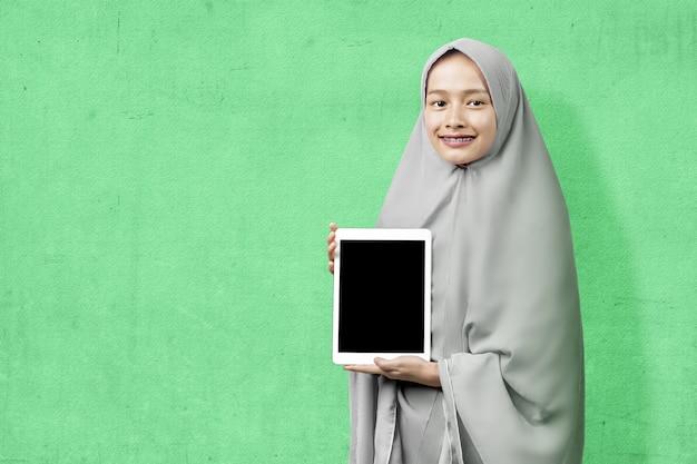 Asiatische muslimische frau im schleier, der leeren tablettbildschirm mit einem farbigen hintergrund zeigt. leerer tablet-bildschirm für speicherplatz