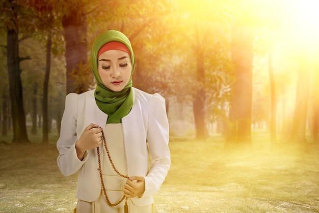 Asiatische muslimische frau im schleier, der mit gebetsperlen auf ihren händen auf dem feld betet