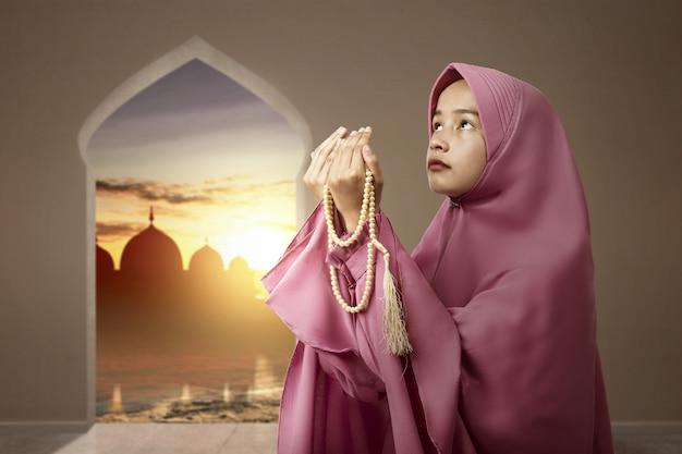 Asiatische muslimische frau im schleier, der mit gebetsperlen auf ihren händen betet