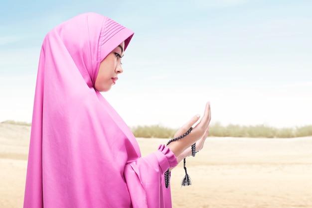 Asiatische muslimische frau im schleier, die mit gebetsperlen auf ihren händen auf der düne betet