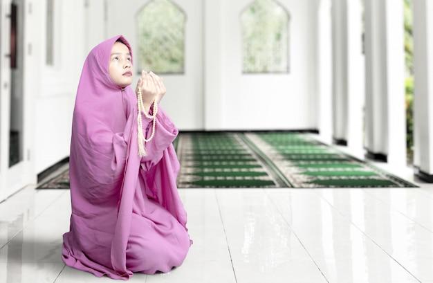 Asiatische muslimische frau im schleier sitzend und betend mit gebetsperlen auf ihren händen