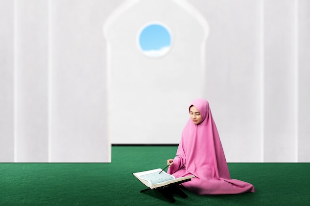 Asiatische muslimische frau in einem schleier, der den koran auf der moschee sitzt und liest