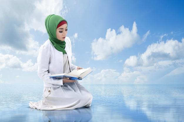 Asiatische muslimische frau in einem schleier, der den koran mit einem blauen himmel sitzt und liest