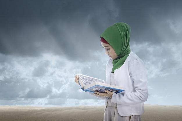 Asiatische muslimische frau in einem schleier, der den koran mit einem dramatischen himmel steht und liest