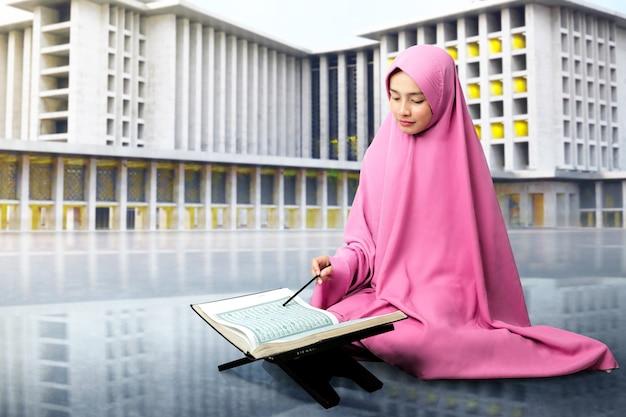 Asiatische muslimische frau in einem schleier, der den koran mit moschee sitzt und liest