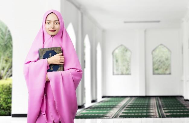 Asiatische muslimische frau in einem schleier, der den koran steht und hält