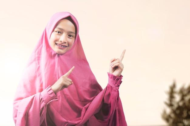 Asiatische muslimische frau in einem schleier, der etwas mit einem sonnenaufgangshimmelhintergrund zeigt. leerer bereich für kopierplatz