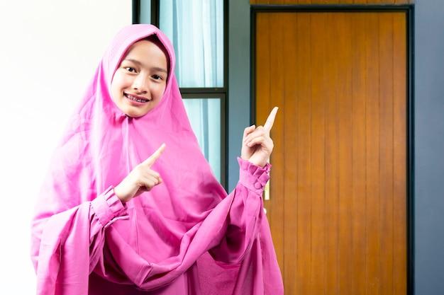 Asiatische muslimische frau in einem schleier, der etwas vor haus zeigt. leerer bereich für den kopierbereich