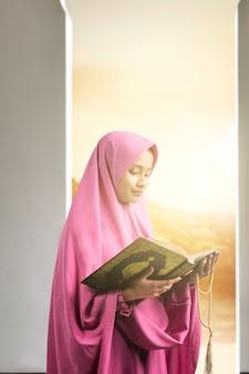 Asiatische muslimische frau in einem schleier, der gebetsperlen hält und den koran auf der moschee liest