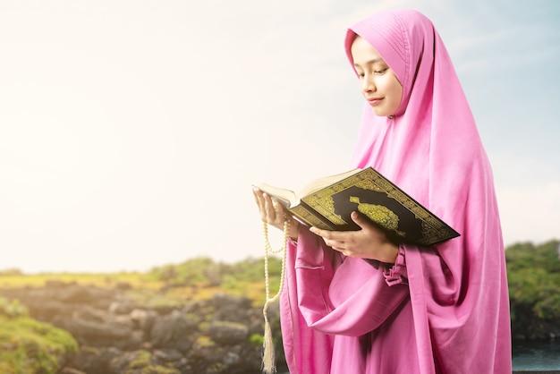 Asiatische muslimische frau in einem schleier, der gebetsperlen hält und den koran im freien liest