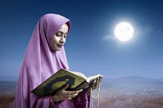 Asiatische muslimische frau in einem schleier, der gebetsperlen hält und den koran liest