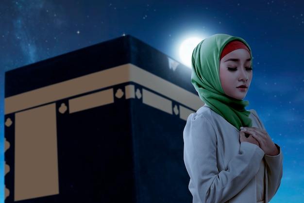 Asiatische muslimische frau in einem schleier, der mit kaaba-ansicht und nachtszenenhintergrund steht und betet