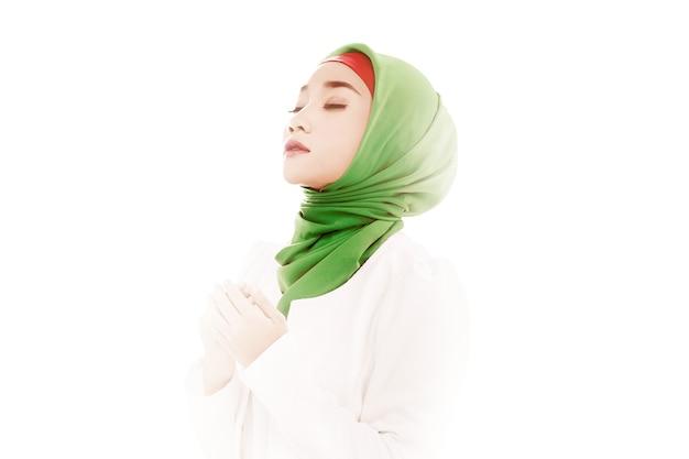 Asiatische muslimische frau in einem schleier, der sitzt, während erhobene hände und mit heller heller oberfläche beten