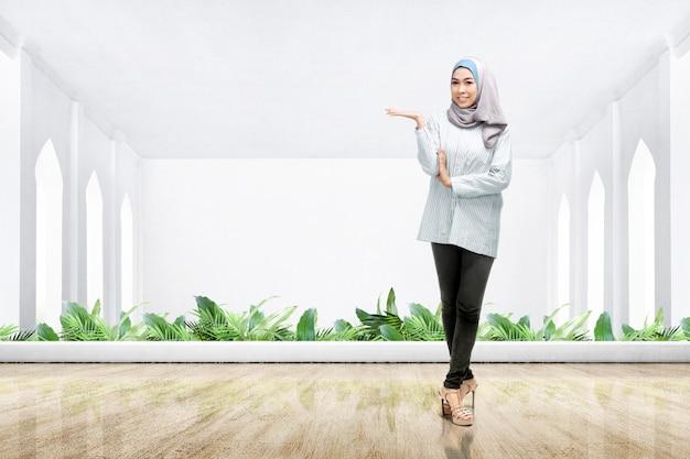 Asiatische muslimische frau in einem schleier stehend und offene handfläche zeigend