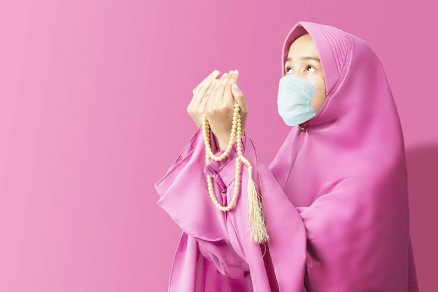 Asiatische muslimische frau in einem schleier und grippemaske, die mit gebetsperlen betet