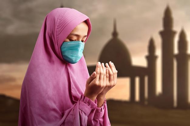 Asiatische muslimische frau in einem schleier und im tragen der grippemaske, während erhobene hände stehen und beten