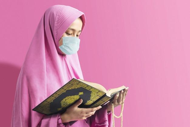 Asiatische muslimische frau in einem schleier und in der grippemaske, die gebetsperlen hält und den koran liest