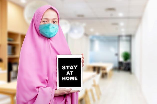 Asiatische muslimische frau in einem schleier und tragen einer grippemaske, die tablette mit einer nachricht für zu hause bleiben auf dem bildschirm zeigt