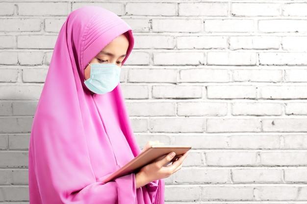 Asiatische muslimische frau in einem schleier und tragen einer grippemaske unter verwendung der tablette