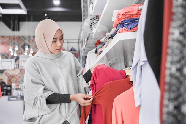 Asiatische muslimische frau kaufen kleidung in der modeboutique