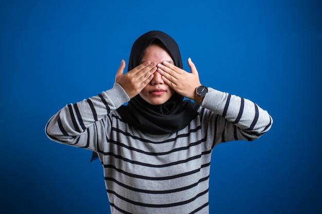 Asiatische muslimische frau mit hijab, die ihre augen mit den händen vor blauem hintergrund bedeckt