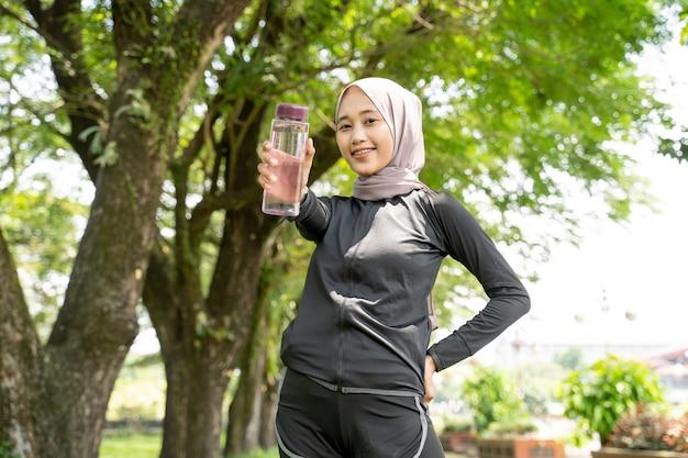 Asiatische muslimische frau mit kopftuch, die während des trainings im freien eine flasche wasser trinkt