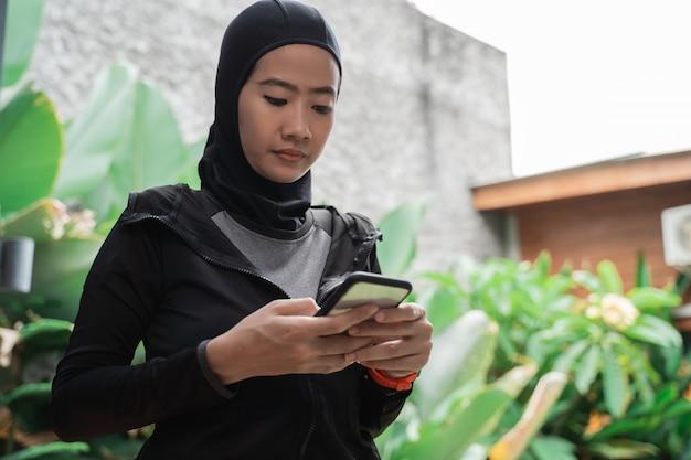 Asiatische muslimische frauen, die hijab-sportbekleidung mit smartphone tragen