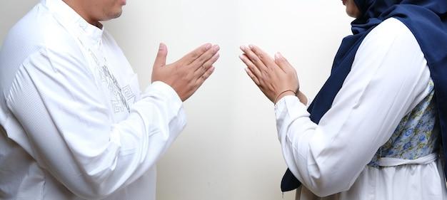 Asiatische muslimische frauen, die hijab tragen und in die kamera lächeln und gestikulieren, um gäste für eid mubarak oder eid fitr oder eid al-fitr . willkommen zu heißen