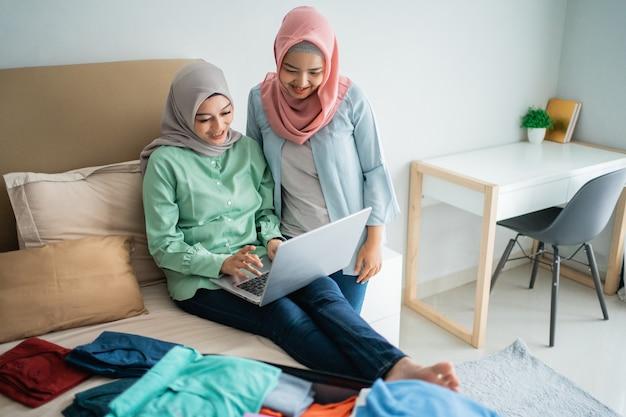 Asiatische muslimische frauen, die laptop mit bett voller kleidung verwenden