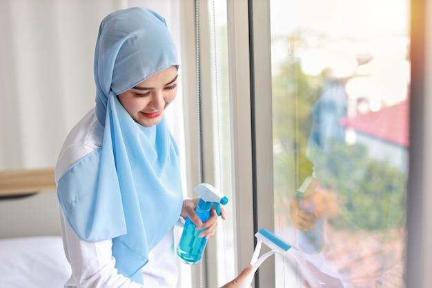 Asiatische muslimische hausfrau frau, die reinigungsspray hält und fensterglas im schlafzimmer wäscht.