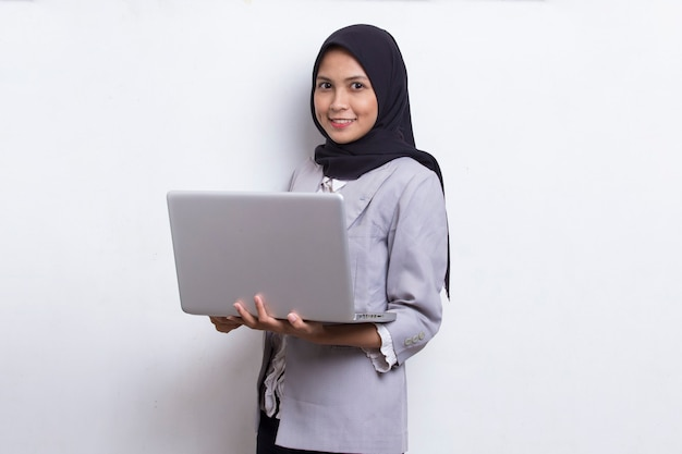 Asiatische muslimische hijab-frau mit ihrem laptop-computer isoliert auf weißem hintergrund