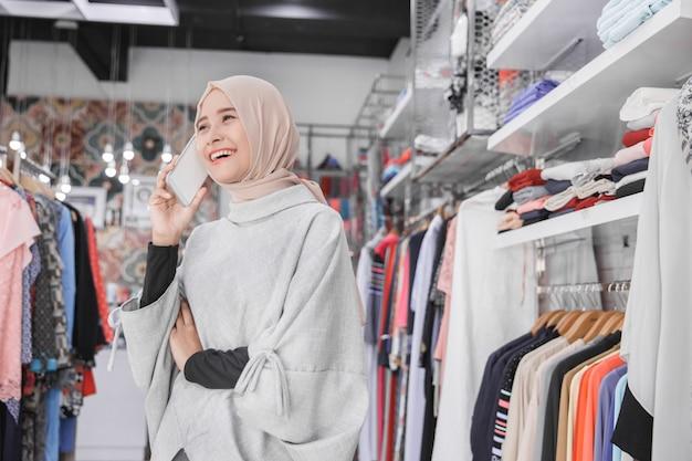 Asiatische muslimische junge frau, die ihr smartphone an der mode st verwendet