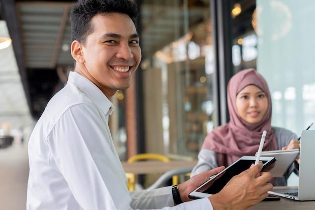 Asiatische muslimische junge studenten, die zusammen studieren