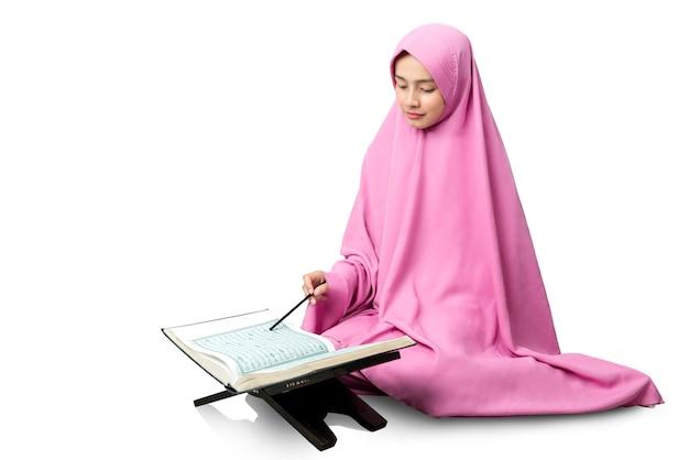 Asiatische muslimische mannfrau in einem schleier, der den koran sitzt und liest
