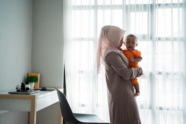 Asiatische muslimische mutter, die ihren kleinen jungen trägt, wenn sie nahe fenster spielt