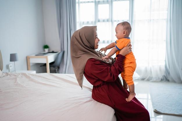 Asiatische muslimische mutter hält ihren kleinen jungen auf dem schoß, wenn sie zusammen spielt