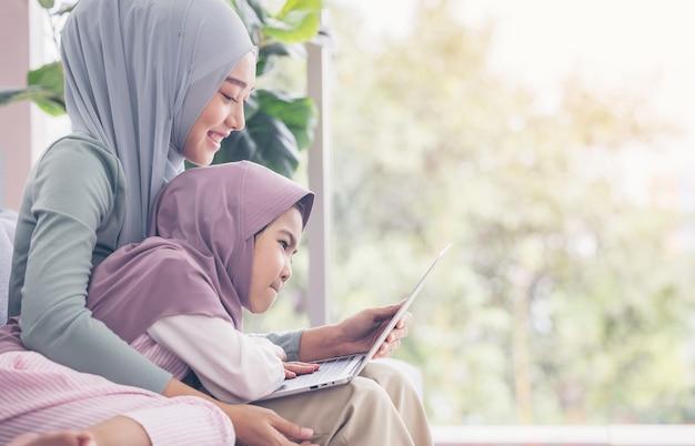Asiatische muslimische mutter und tochter lächeln, wenn sie laptop zusammen benutzen