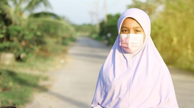 Asiatische muslimische studentin, die hijab und gesichtsmaske trägt, um covid19-coronavirus oder staub zu verhindern pm2